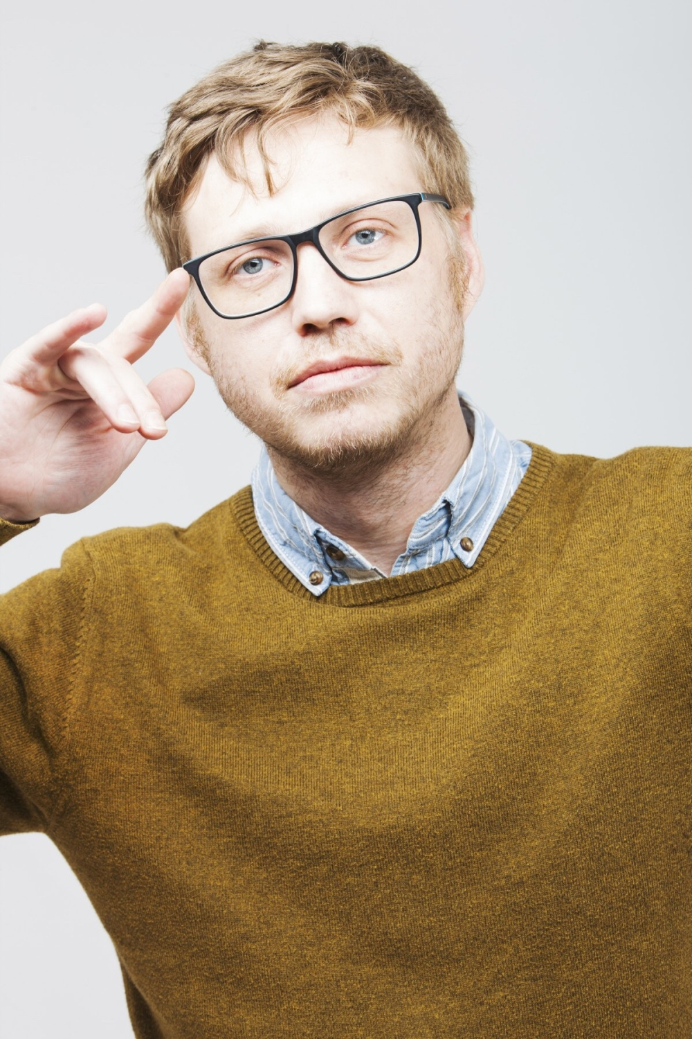 Blonde businessman with black acrylic frames in a mustard yellow sweater with his right hand raised thoughtfully.