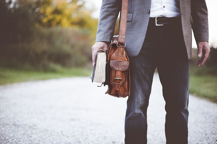 A torso down photo of a white man in business casual gray suiting carrying a thick book and his brown messenger bag as he walks down a verdant road.