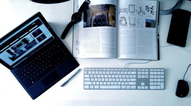 Laptop, magazine, keyboard, and notebook spread out across a workspace.