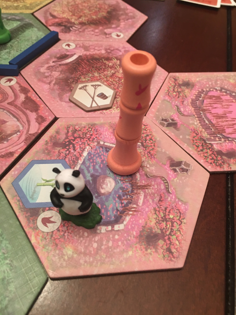 Panda figurine on tiles with pink bamboo pieces.