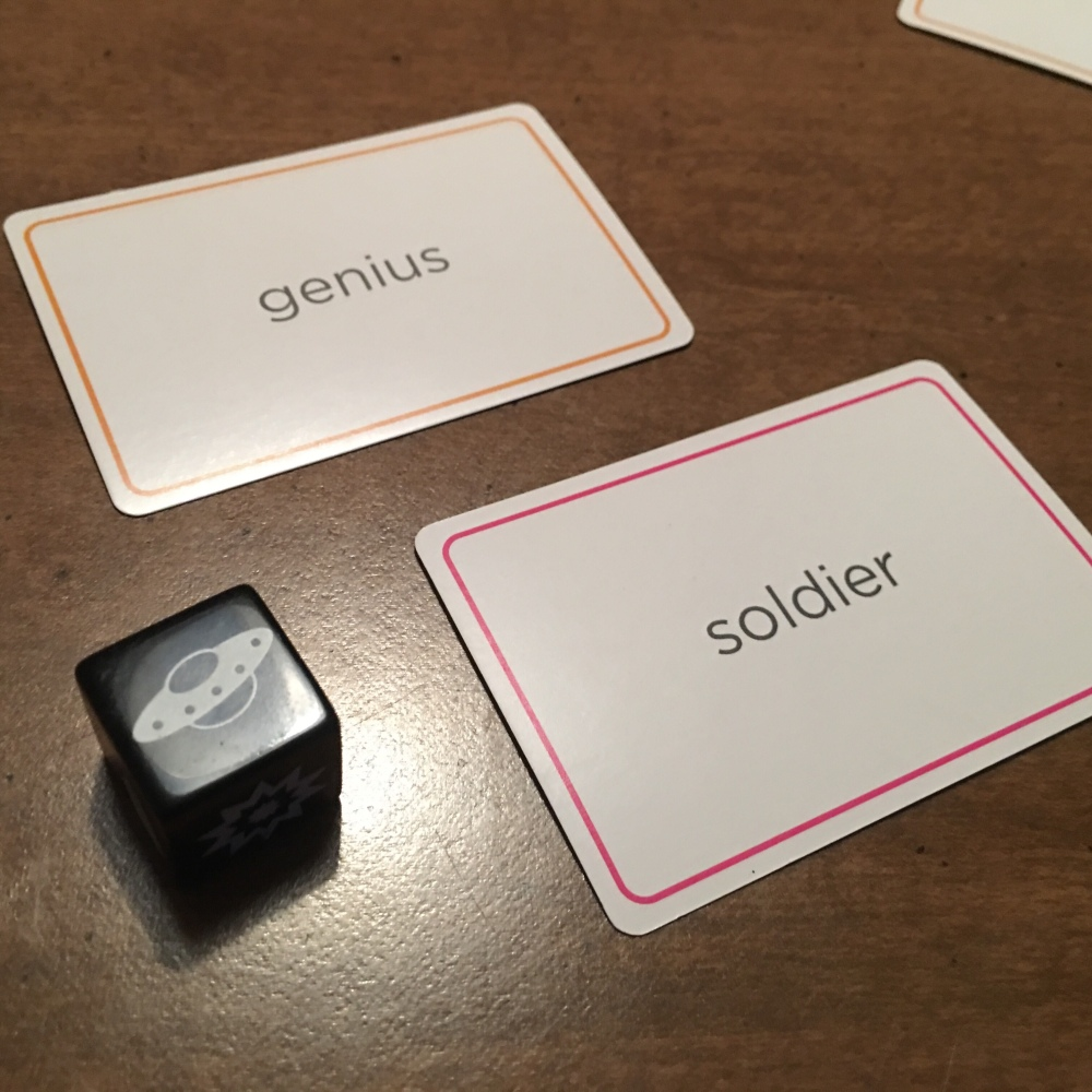 Image description: a UFO symbol on a die to indicate Sci-Fi with the cards Genius & Soldier.
