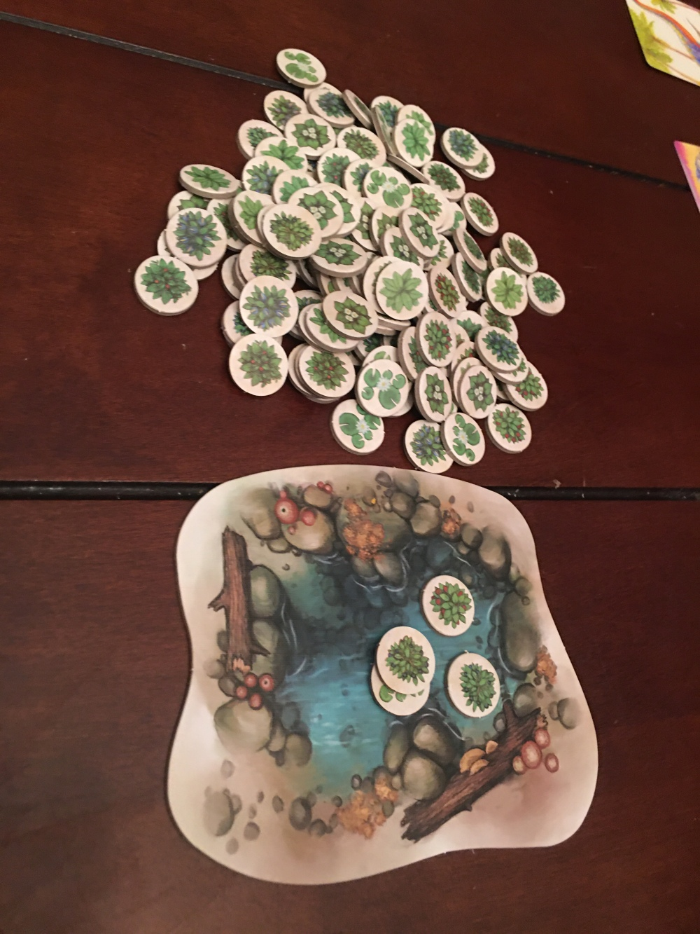 Watering hole game piece with leafy food tokens.