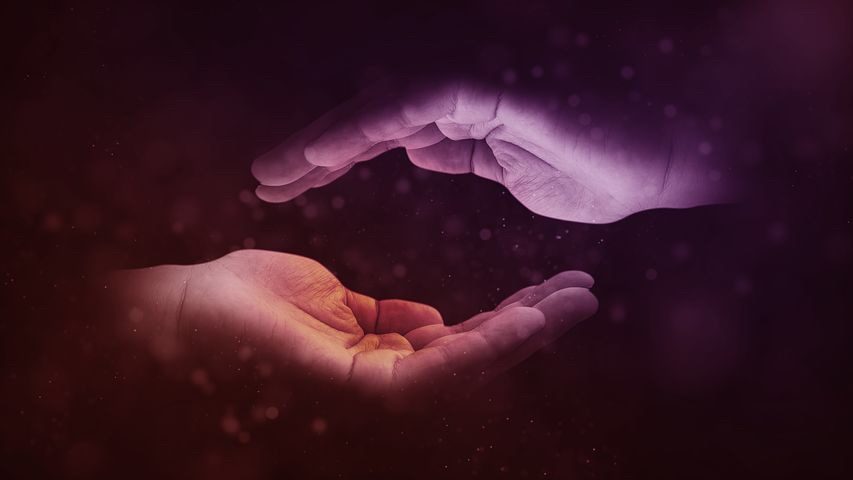 Image: two cupped hands parallel, one over the other, in dark lighting.