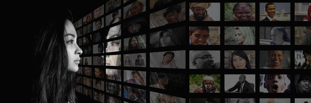 Image: a young woman with long, dark hair looking to her right at a large grid of images of people's faces.